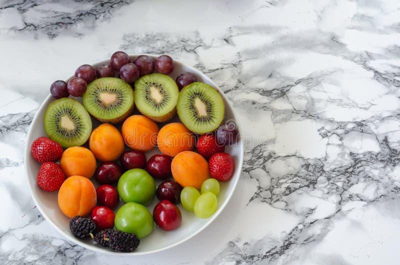 Nya färgrika frukter i den vita plattan Sund näring, bantar Co arkivfoton