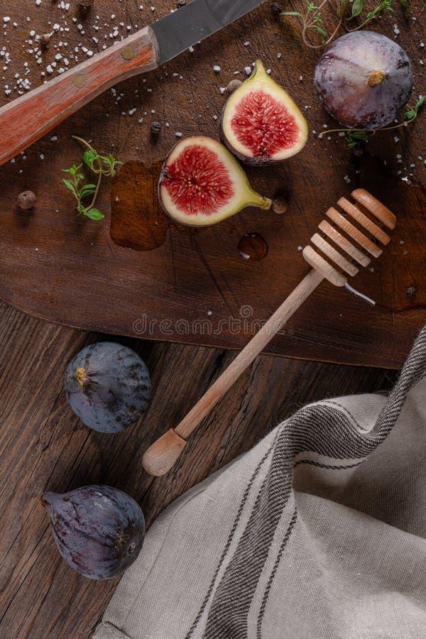 nya figs Hela fikontr?d och skivat i halva fikontr?d och timjansidor p? tr?sk?rbr?da royaltyfria bilder