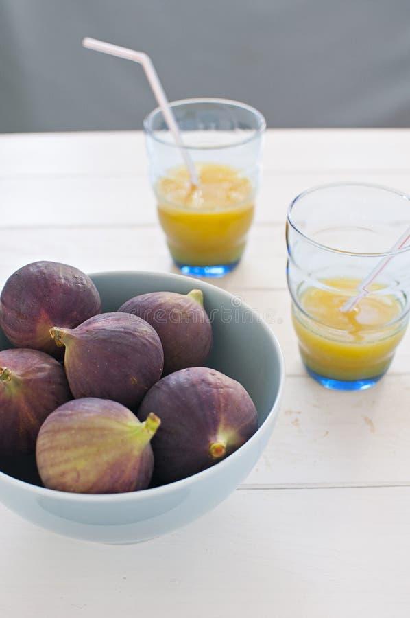 Nya figs i turkos bowlar med orange fruktsaft royaltyfria bilder