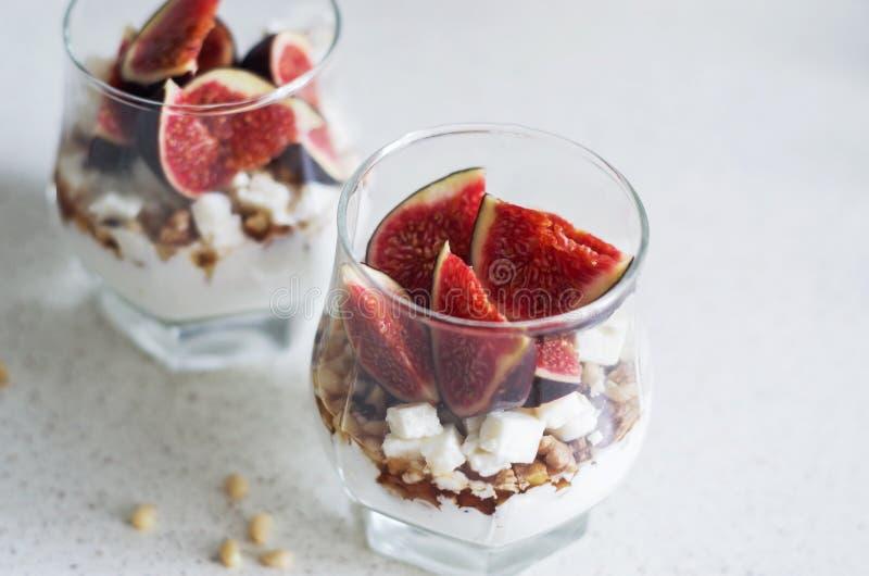 Nya fikonträd med vanilj piskad kräm, ost, muttrar och lönnsirap i en glass dryckeskärl sund dryck Sund mat som bantar och royaltyfri foto