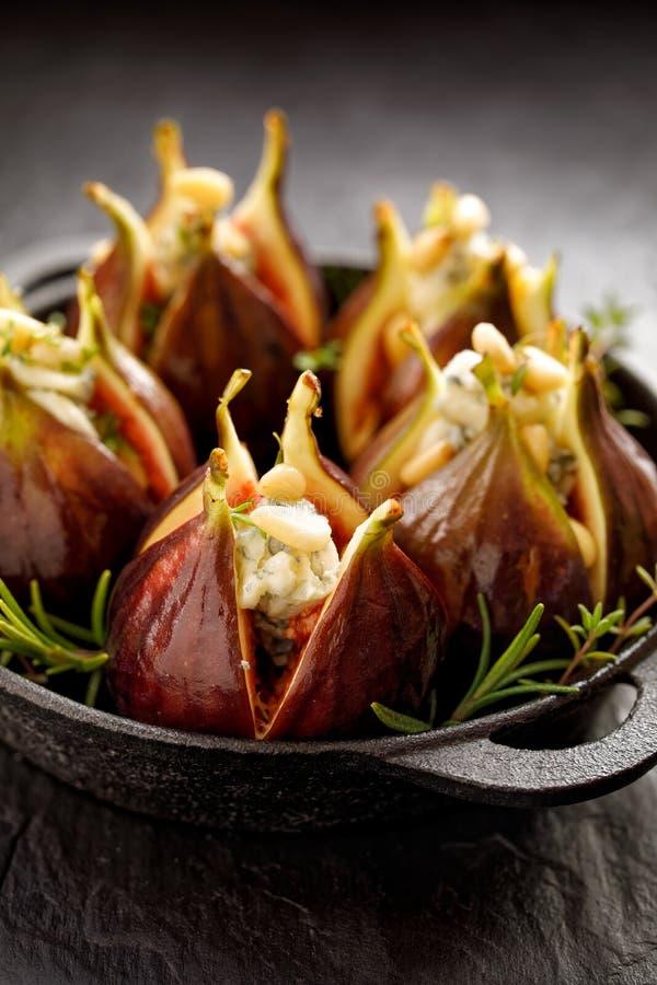 Nya fikonträd som stoppas med gorgonzola ost, sörjer muttrar och örter i en svart maträtt på ett mörkt, stenjordning, tätt upp royaltyfri fotografi