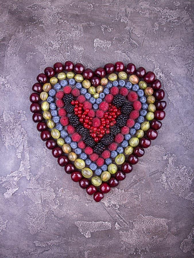 Nya frukter och bär i hjärtaform över på betonggrå färglodisar royaltyfri bild