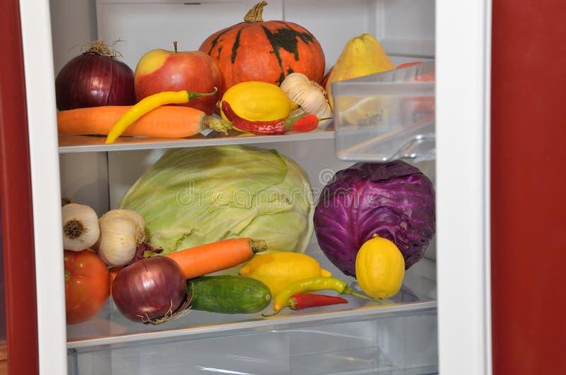 Nya frukter och grönsaker i halva-öppnat kylskåp arkivbilder