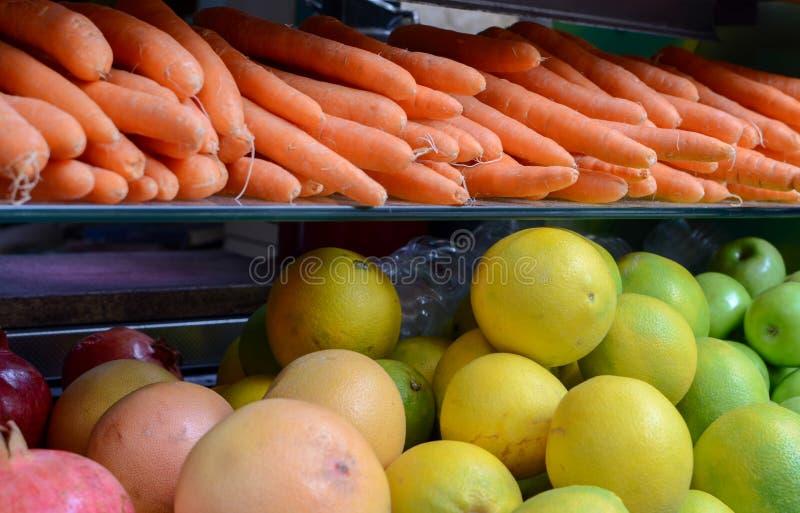 Nya frukter och grönsaker visade framme av fruktsafter som lagret på bönder marknadsför royaltyfri foto