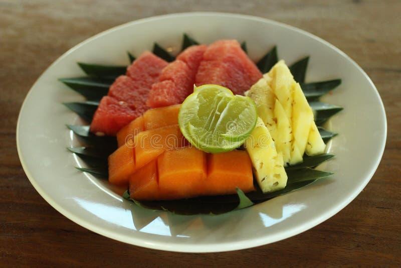 Nya frukter på den vita plattan med naturlig bananbladordning Klippta sunda frukter, papaya, vattenmelon, ananas på en platta arkivfoto
