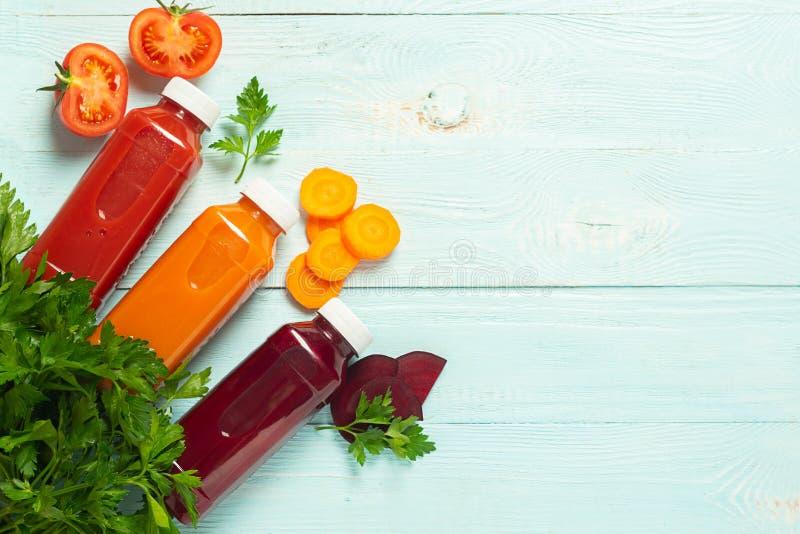 Nya fruktsaftsmoothies från en variation av beta för tomater för grönsakmorotäpple i flaskor på en träblå bakgrund arkivbilder
