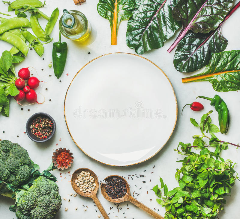Nya gräsplaner, rå grönsaker och korn, vit platta i mitt arkivfoto