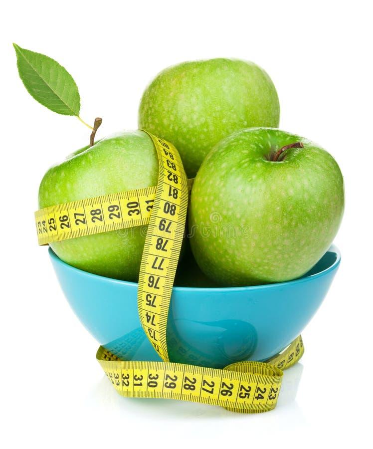 Nya gröna äpplen med det gula mäta bandet royaltyfri bild
