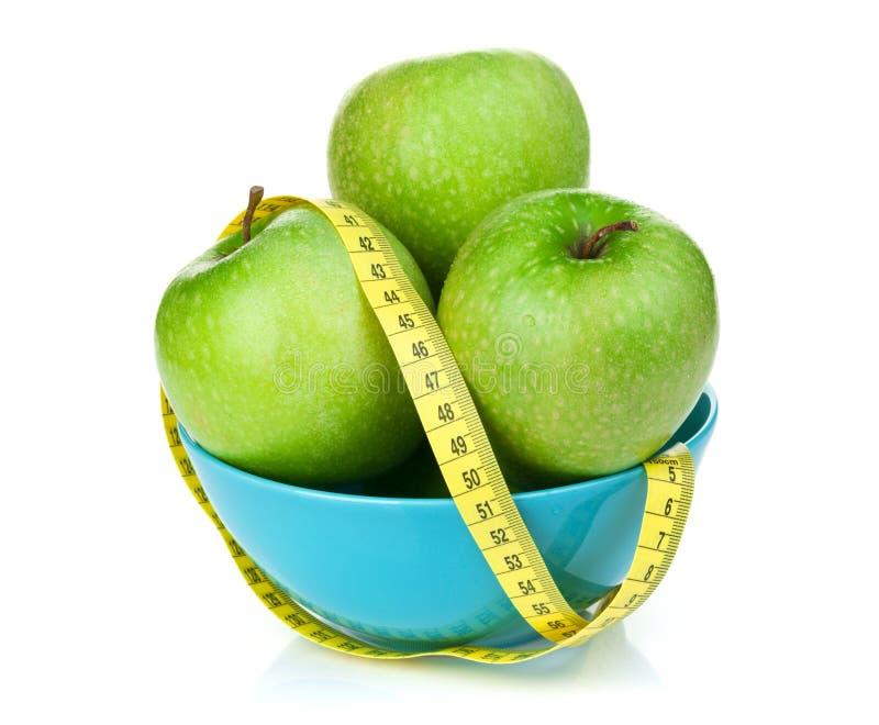 Nya gröna äpplen med det gula mäta bandet arkivfoto