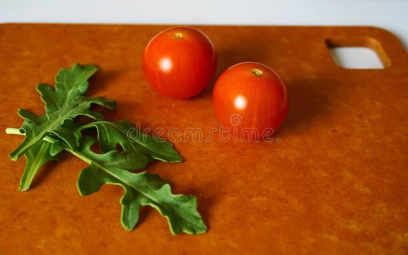Nya gröna arugulasidor och körsbärsröda tomater på hardboard royaltyfri fotografi