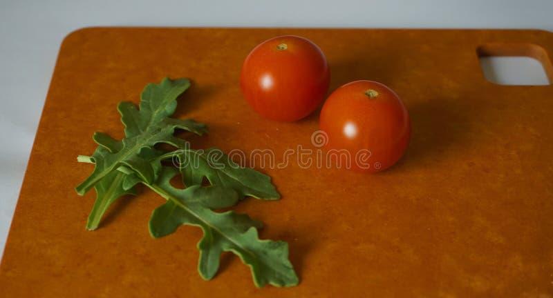 Nya gröna arugulasidor och körsbärsröda tomater på hardboard royaltyfri bild