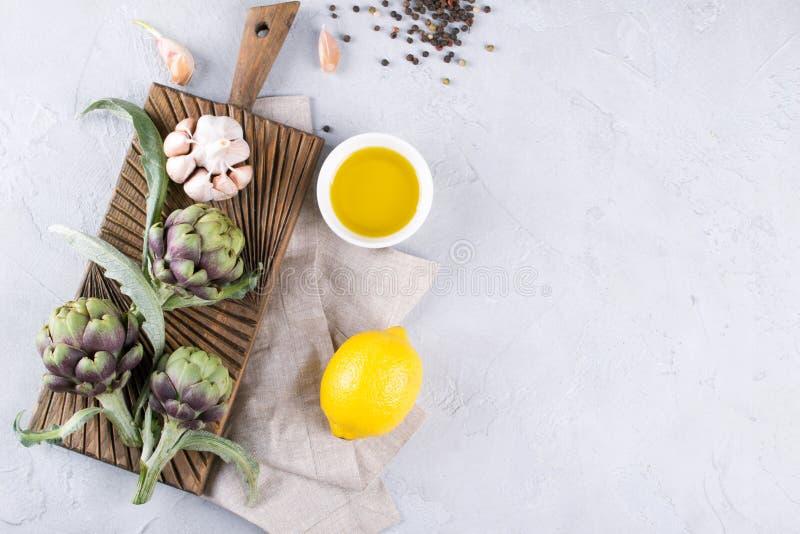Nya gröna kronärtskockor på skärbrädan som är klar att laga mat, och ingredienser vitlök, citron och olivolja royaltyfri bild
