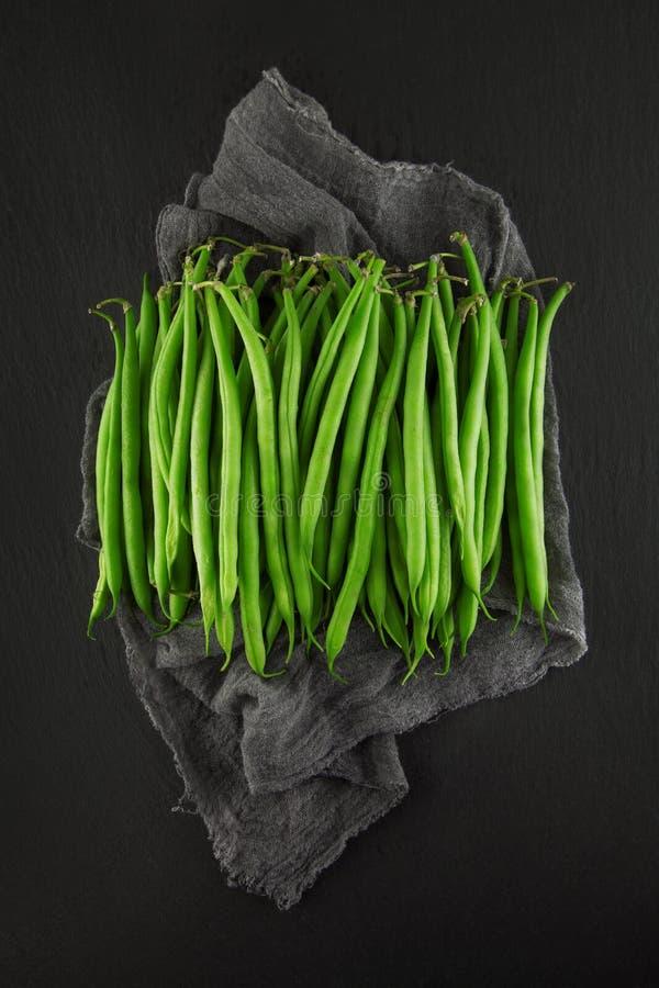 Nya gröna prinsessabönor på mörker kritiserar kökplattan, rostig sjaskig stil arkivbilder