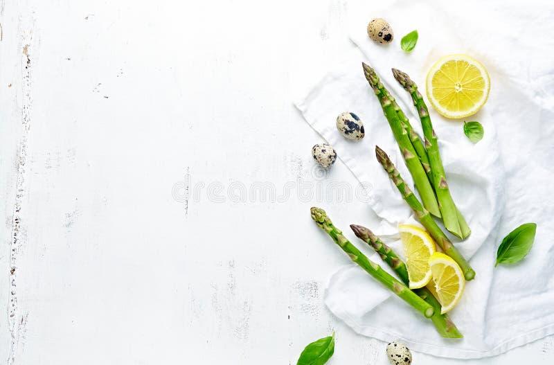 Nya gröna sparris-, citron- och vaktelägg på vit träbakgrund Symbolisk bild Lekmanna- l?genhet arkivfoton