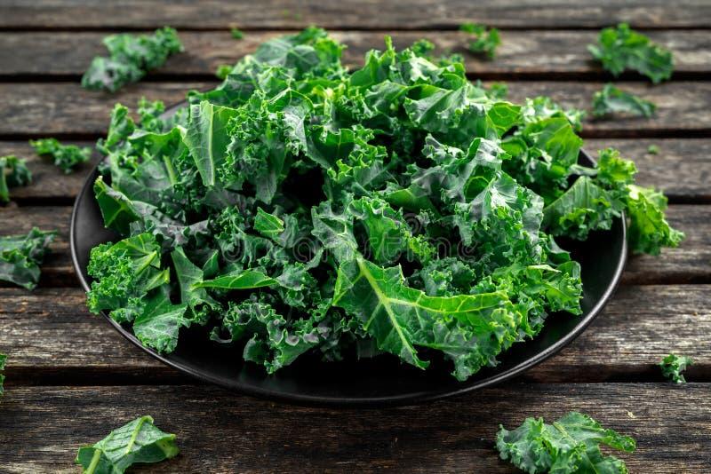 Nya gröna sunda sidor för superfoodgrönsakgrönkål i en svart platta på den trälantliga tabellen royaltyfri foto