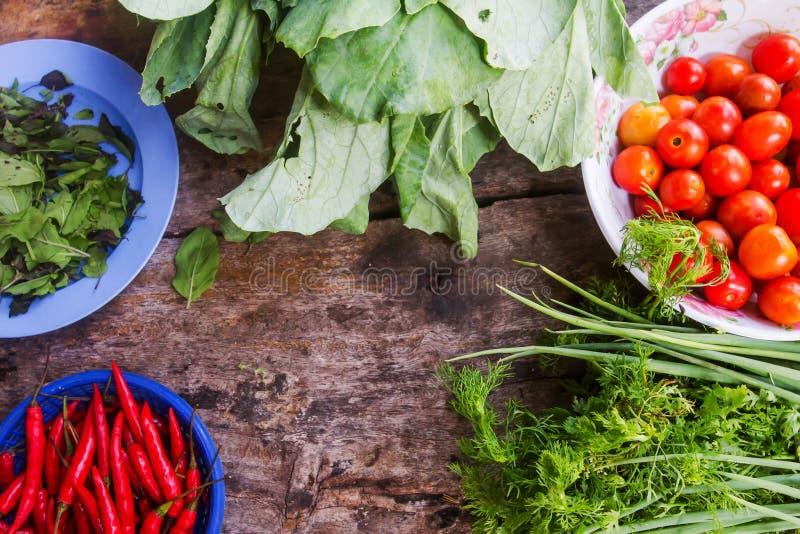 Nya grönsaker är delar i matlagning förlades på ett trägolv arkivbilder
