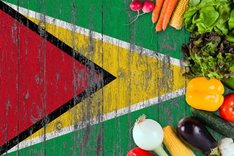 Nya grönsaker från Guyana på tabellen Laga mat begrepp p? tr?flaggabakgrund royaltyfri bild
