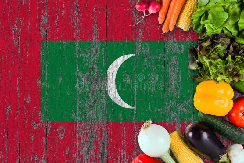 Nya grönsaker från Maldiverna på tabellen Laga mat begrepp p? tr?flaggabakgrund arkivfoto