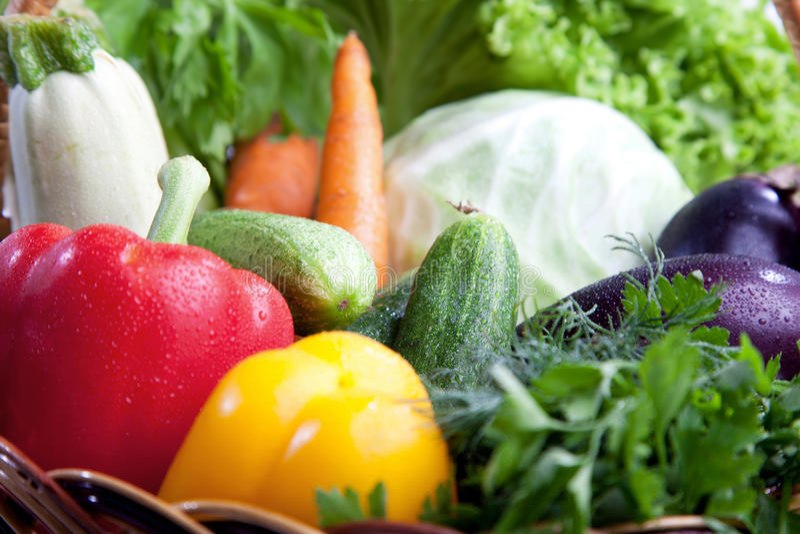Nya grönsaker i en korg på white. royaltyfria foton
