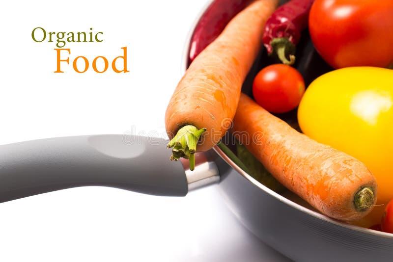 Nya grönsaker i en kruka på vit bakgrund arkivfoto