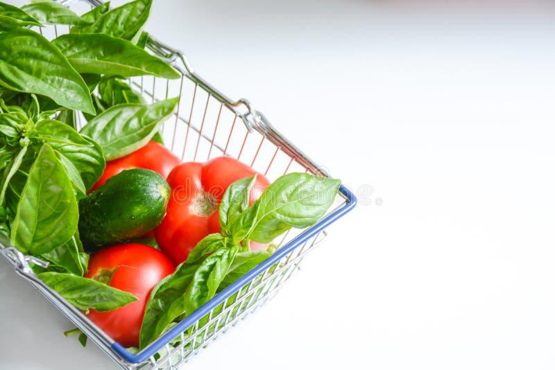 Nya grönsaker i shoppingvagnen som isoleras på vit bakgrund royaltyfria bilder