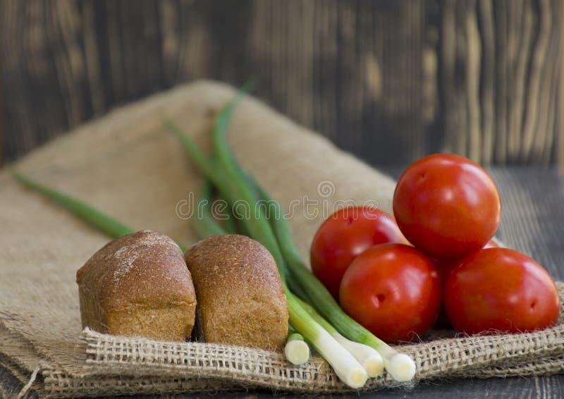 Nya grönsaker och bröd på säckvävbakgrund arkivbilder