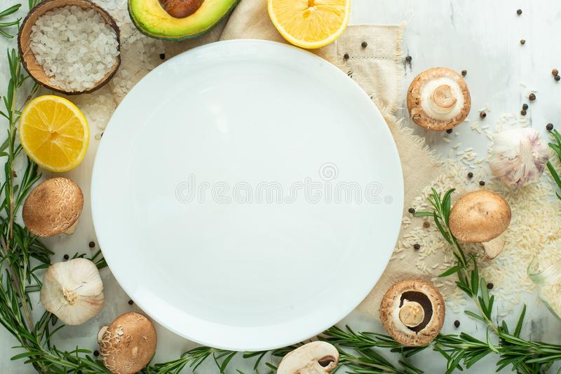 Nya grönsaker och champinjoner runt om en vit platta för designen, bästa sikt, utrymme för kopia Sund ren mat, strikt vegetarian, arkivfoton