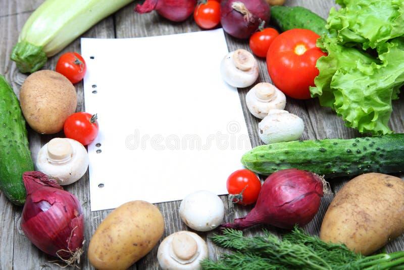 Nya grönsaker och ett papper för recept arkivbild