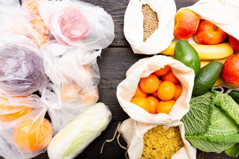 Nya grönsaker och frukter i ecobomullspåsar mot grönsaker i plastpåsar Nollförlorat begrepp - bruksplastpåsar eller mång- royaltyfria bilder