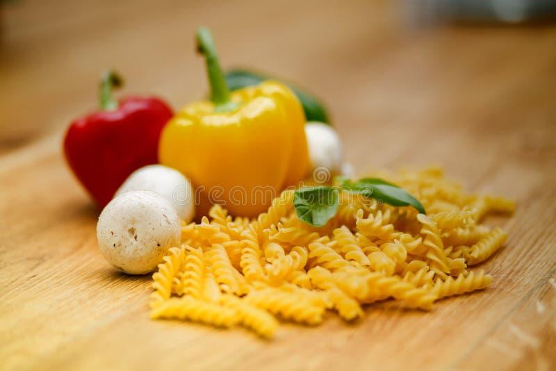 Nya grönsaker och pasta som ligger på en trätabell royaltyfri foto