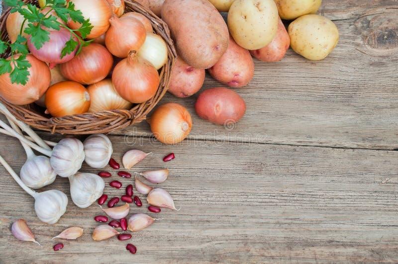 Nya grönsaker på en trätabell: lökar potatisar, vitlök royaltyfria bilder