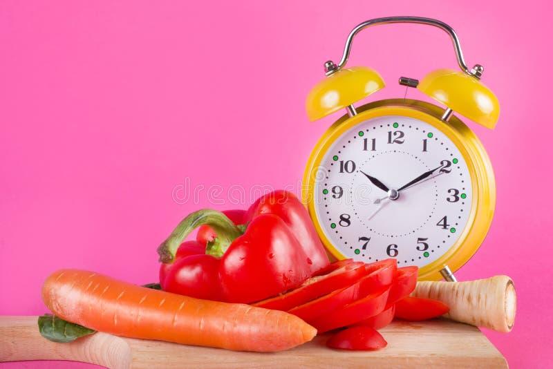 Nya grönsaker på ett träkökbräde och en retro klocka som isoleras på rosa färger royaltyfri bild
