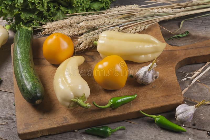 Nya grönsaker pepprar, tomater, zucchini på en träbräderåkost Strikt vegetarianmat fotografering för bildbyråer