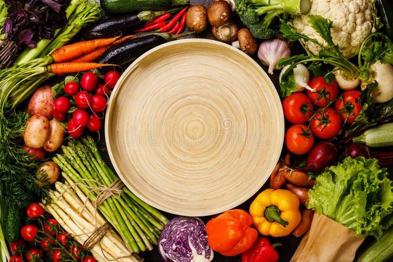 Nya grönsaker runt om bambumagasinet royaltyfri foto