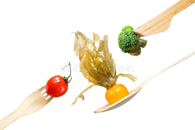 Nya grönsaker tomat, broccoli, physalis på trägaffeln, kniv, sked arkivbilder