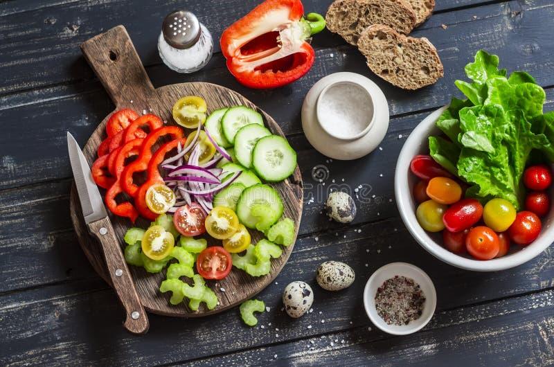 Nya grönsaker - tomater, gurkor, peppar, selleri och trädgårdörter och kryddor på mörk träbakgrund arkivbilder