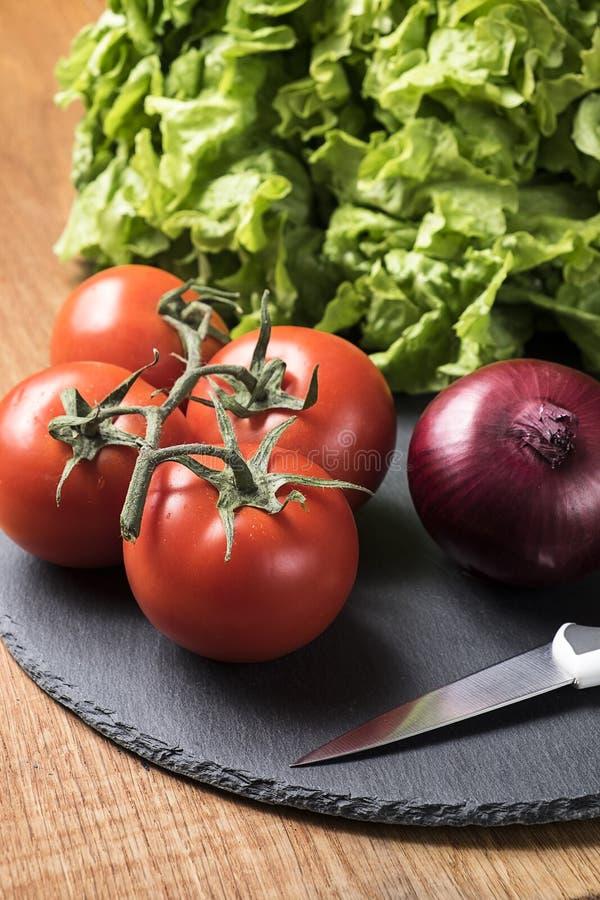 Nya grönsaker - tomater, lök och grönsallat royaltyfria foton