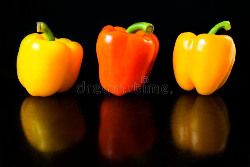 Nya grönsaker tre apelsin som är gul, paprikor på en svart bakgrund royaltyfria foton