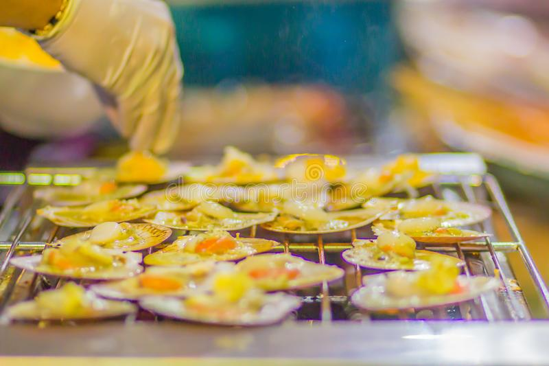 Nya grillade kammusslor i kammusslaskal med chili, smör, vitlök, ost och spenat Bakade kammusslor med smörkammusslaskalet royaltyfri bild