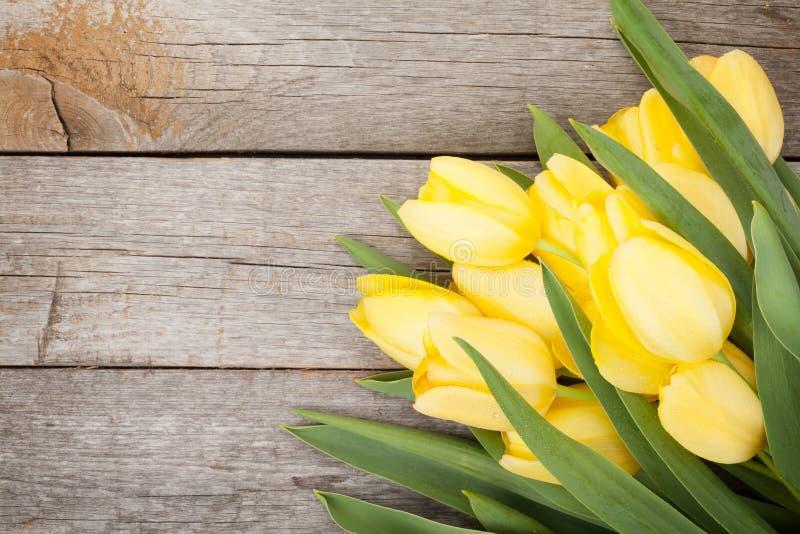 Nya gula tulpan över trätabellen royaltyfria foton