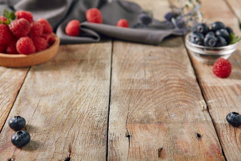 Nya härliga hallon och blåbär på gammalt lantligt trä arkivbilder