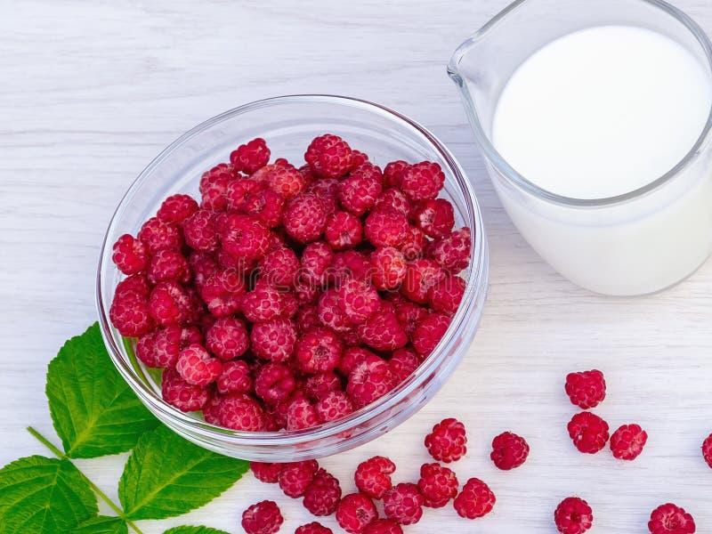 Nya hallon i en exponeringsglasbunke och en naturlig iogurt på en vit trätabell äta för begrepp som är sunt royaltyfri bild
