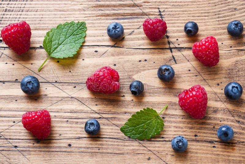 Nya hallon och blåbär i en träbakgrund royaltyfri bild