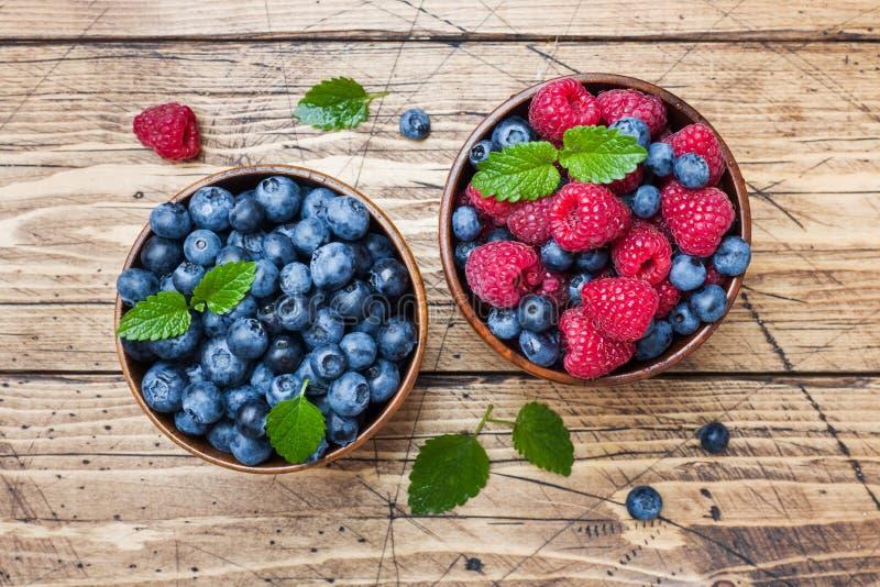 Nya hallon och blåbär i en träplatta royaltyfri bild