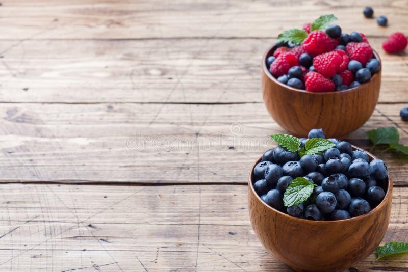 Nya hallon och blåbär i en träplatta arkivbild