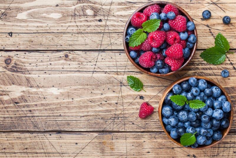 Nya hallon och blåbär i en träplatta royaltyfri foto