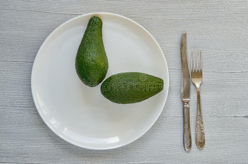 Nya hela avokadon på den vita plattan Sund mat på grå bakgrund arkivfoto