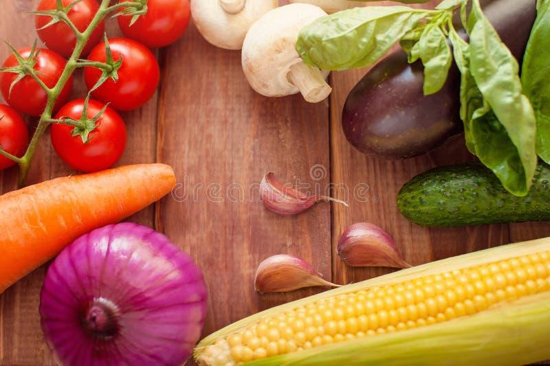 Nya ingredienser för att laga mat i lantlig inställning: tomater, basilika, olivolja, vitlök och lök, kål, letttuce royaltyfria foton