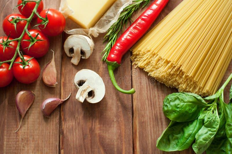 Nya ingredienser för italiensk kokkonst: pasta, tomater, basilika, champinjoner, vitlök och lök royaltyfri fotografi