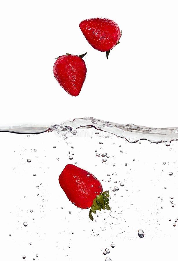 Nya jordgubbar, i att falla i vatten på arkivfoto